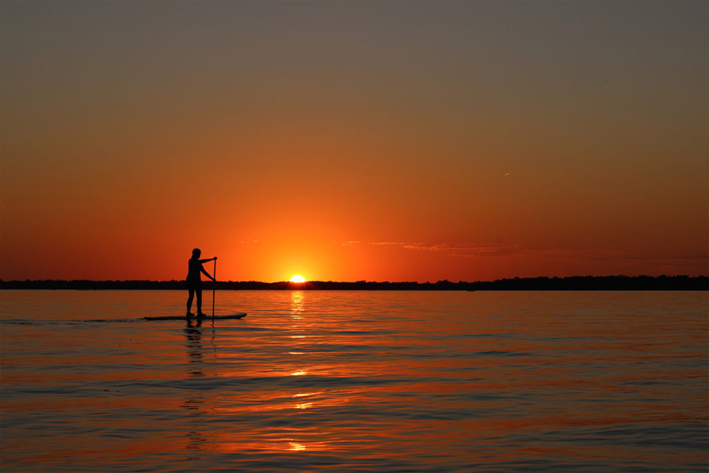 Person on a paddle board on a lake at sunset