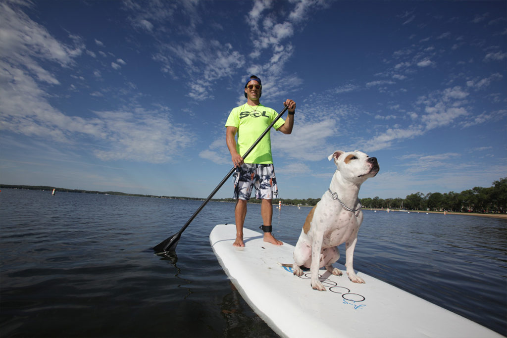 Man and dog on a standup paddle board